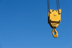 A yellow crane hook suspended against a blue sky Stock Photos