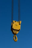 A yellow crane hook suspended against a blue sky Royalty Free Stock Image