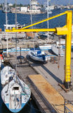 Yellow crane, sailing yachts and pleasure boats, Varna port Stock Photos