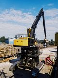 Fast yellow crane unloading logs in the port from cargo vessel stock image