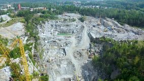 Yellow cranes rides in granite quarry, working process in granite quarry. 4K aerial view