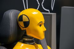 Yellow crash test dummy. In a car seat royalty free stock photography