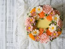 Yellow cream cake decorated with buttercream flowers - peonies, roses, chrysanthemums, scabiosa, carnations - on white wooden back stock image