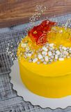 Yellow cream cheese cake with caramel decoration and gypsophila Stock Photo