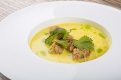 Yellow cream soup served with croutons royalty free stock photo