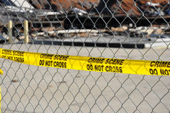 Yellow Crime Scene Do Not Cross Tape. A bright yellow warning tape that reads Crime Scene Do Not Cross on a chain link fence Stock Photo