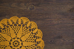 Yellow crochet doily over dark wood Royalty Free Stock Photography