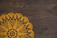 Yellow crochet doily over dark wood. Yellow crochet doily  over  dark wood Royalty Free Stock Photography