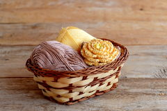 Yellow crochet flower with brown leaves and beads, cotton yarn in wicker basket on old wooden background. Crochet flower pattern Stock Photo
