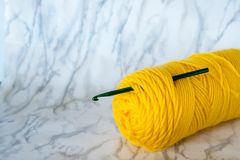 Yellow crochet yarn with crochet hook on neutral background Royalty Free Stock Photos