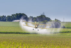 Yellow Crop Duster. A crop duster applies chemicals to a field of vegetation royalty free stock photography
