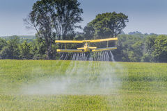 Yellow Crop Duster. A crop duster applies chemicals to a field of vegetation Stock Photos