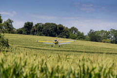 Yellow Crop Duster. A crop duster applies chemicals to a field of vegetation Stock Photography