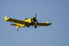 Yellow Crop Dusting Plane Flying in a Blue Sky Royalty Free Stock Image