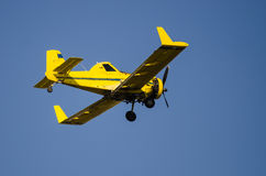 Yellow Crop Dusting Plane Flying in a Blue Sky Royalty Free Stock Photography