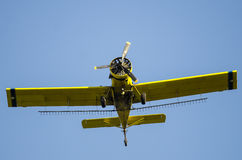 Yellow Crop Dusting Plane Flying in a Blue Sky Royalty Free Stock Photos