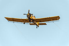 Yellow Cropduster. Camera catches a yellow crop duster in flight, while spraying mosquitoes. Low angle view over clear blue sky. All inscriptions (company names Stock Photography