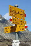 Yellow cross. Yellow traffic signplaced in high mountain on the borderline between italy and switzerland Stock Images