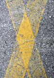 Yellow cross on asphalt Stock Photography