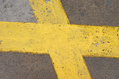 Yellow cross on gray concrete floor Royalty Free Stock Image