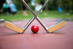 Yellow crossed iron rackets and a red ball at a minigolf court a. Two yellow crossed iron rackets and a red ball at a minigolf court at a sunny day stock images