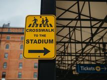 Yellow crosswalk to the stadium sign pointing to the right near a ballpark royalty free stock photos
