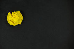 Yellow crumpled paper ball on a black background Stock Photos