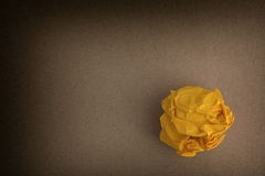 Yellow crumpled paper ball on a brown background Stock Photos