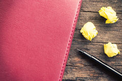 Yellow crumpled papers put on wooden with note and pen Royalty Free Stock Image