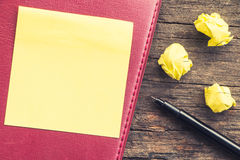 Yellow crumpled papers put on wooden with note and pen Stock Photos