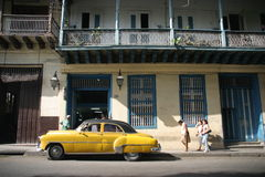 Yellow Cuban Old-timer. An old yellow old-timer in front of building at the streets of havana stock photo