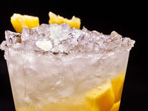 Yellow cube ice of cold drink  with  pineapple on dark background. Royalty Free Stock Photo