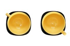 Yellow cup and black saucer, top view Stock Images