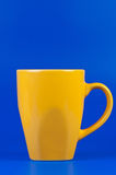 Yellow cup on blue background. Stock Image