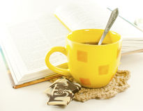 Yellow cup and book. Yellow cup of tea with chocolate and book Royalty Free Stock Photos