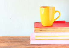 Yellow cup of coffe on old vintage books Stock Images