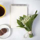 Yellow cup of coffee, a bouquet of lilies of the valley, a notepad for notes and a saucer with two brownie cookies. Breakfast. Cop Stock Image