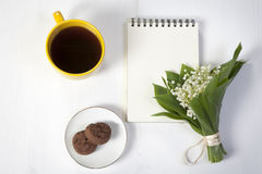 Yellow cup of coffee, a bouquet of lilies of the valley, a notepad for notes and a saucer with two brownie cookies. Breakfast. Cop Stock Images