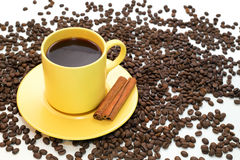 Yellow cup of coffee,cinnamon and coffee beans Royalty Free Stock Photos
