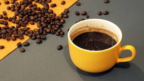 Yellow cup of coffee on a gray and yellow background with coffee beans stock image