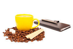 Yellow cup of coffee and notebook Stock Image