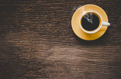 A yellow cup of coffee on old wooden table. royalty free stock photography