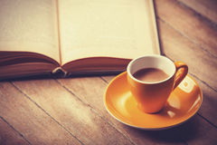 Yellow cup of the coffee and vintage book. Royalty Free Stock Photos