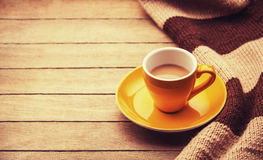 Yellow cup of the coffee and vintage scarf. Stock Photo