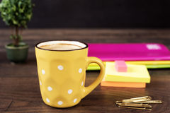 Yellow cup of coffee with white dots. Pretty pink office accessories - notebooks, gold pins, stickers, rubber and polka dot mug. On a wooden desk royalty free stock photos