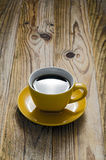 Yellow Cup. Of coffee on a wooden table Royalty Free Stock Images