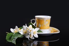 Yellow cup and flowers. Yellow cup on black with jasmine flower Royalty Free Stock Photo