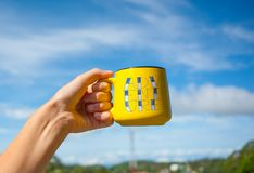 Yellow cup in hand with Adventure lettering. Object over nature background, beautiful motivation photo stock photography