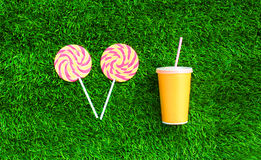 Yellow cup of juice with straw and two colorful lollipop caramel on stick over green textured grass Royalty Free Stock Images