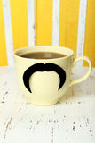 Yellow cup with paper mustache and coffee on white wooden background. Royalty Free Stock Photos